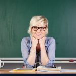 21266077 – confident young blond female teacher against chalkboard