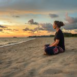 41846180 – woman sitting on beach sand and relaxing at sunset time