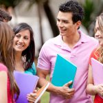 9514016 – group of students talking and holding notebooks outdoors