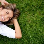 12393731 — woman relaxing outdoors looking happy and smiling