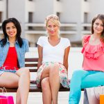 21829859 – three beautiful women in the city sitting on a bench and smiling .